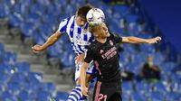 Pemain Real Madrid, Martin Odegaard, duel udara dengan pemain Real Sociedad, Robin Le Normand, pada laga Liga Spanyol di Stadion Anoeta, Minggu (20/9/2020). Kedua tim bermain imbang 0-0. (AP/Alvaro Barrientos)