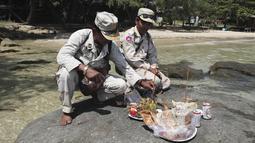 Tentara Kamboja berdoa dengan harapan menemukan warga negara Inggris Amelia Bambridge di pulau Koh Rong di barat daya Kamboja (29/10/2019). Amelia Bambridge hilang ketika menghadiri pesta pantai di pulau Koh Rong yang diikuti wisatawan dari berbagai negara. (AP Photo/Heng Sinith)