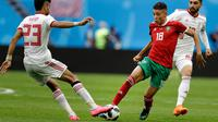 Pemain Maroko Amine Harit berusaha melewati pemain Iran Ramin Rezaeian saat bertanding pada grup B Piala Dunia 2018 di St Petersburg Stadium, Rusia, (15/6). Iran menang tipis 1-0 berkat gol bunuh diri Aziz Bouhaddouz. (AP Photo/Andrew Medichini)