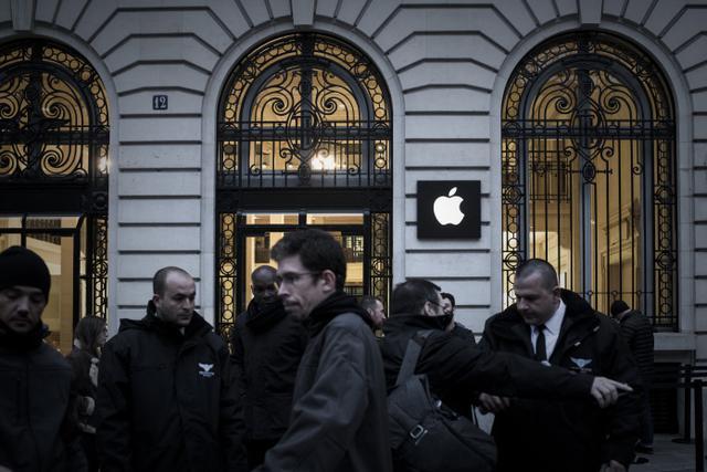 Karyawan Apple berdiri di luar toko Apple pada hari peluncuran iPhone X di Paris pada 3 November 2017. Philippe Lopez/AFP
