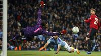 Kiper Manchester United David de Gea berusaha menepis bola sundulan striker Manchester City, Sergio Aguero pada pertandingan semifinal Piala Liga Inggris di stadion Etihad, Manchester, Rabu (29/1/2020). MU menang 1-0 atas City namun gagal ke final karena skor agregat 3-2. (AP Photo/Dave Thompson)