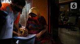 Warga penerima bantuan menandatangani bukti pemberian bantuan sosial tunai (BST) di RW 05 Kelurahan Kenari, Senen, Jakarta, Rabu (6/1/2021). Pencairan BST untuk empat bulan kedepan sebesar Rp300 ribu per Keluarga Penerima Manfaat (KPM) diberikan langsung kepada warga. (Liputan6.com/Johan Tallo)