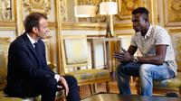 Presiden Prancis Emmanuel Macron (kiri) berbincang dengan Mamoudou Gassama di Istana Elysee, Paris, Prancis, Senin (29/5). Imigran asal Mali tersebut memperoleh penghargaan setelah menyelamatkan seorang balita di Paris. (AP Photo/Thibault Camus, Pool)