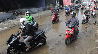 Pengendara motor menghindari lubang yang cukup dalam akibat jalan yang rusak di Jalan Raya Bojonggede, Bogor Senin (11/5/2020). Beberapa titik jalan yang menghubungkan Citayam Depok - Bojonggede Bogor mengalami kerusakan yang cukup parah sejak tiga bulan terakhir. (merdeka.com/Arie Basuki)