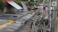 Pekerja mengerjakan proyek revitalisasi trotoar di kawasan Kemang, Jakarta Selatan, Selasa (15/10/2019). Pemerintah Provinsi DKI menargetkan pelebaran dan penataan trotoar ini akan rampung pada Desember 2019. (Liputan6.com/Herman Zakharia)
