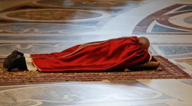 Paus Fransiskus berdoa sambil berbaring di lantai dalam prosesi Jumat Agung memperingati penyiksaan Yesus sebelum disalibkan di Basilika Santo Petrus, Vatikan, Jumat (19/4). (AP Photo/Alessandra Tarantino)