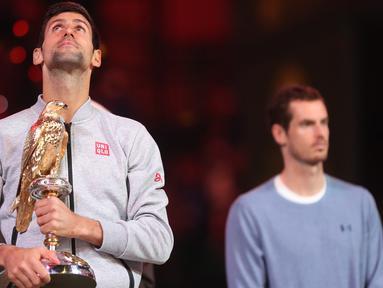 Petenis Serbia, Novak Djokovic (kiri) berpose dengan trofi Qatar Open 2017 usai menaklukkan petenis Skotlandia, Andy Murray dalam final turnamen Qatar Terbuka di Doha, Sabtu (7/1). Djokovic berhasil menang dengan skor 6-3, 5-7, 6-4. (KARIM Jaafar/AFP)