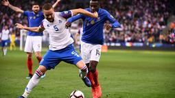 Bek Islandia, Sverrir Ingason hentikan pergerakan Matuidi pada laga kedua Kualifikasi Piala Eropa 2020 Grup H yang berlangsung di Stadion Stade de France, Paris, Selasa (26/3). Perancis menang 4-0 atas Islandia. (AFP/Franck Fife)