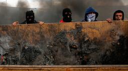 Demonstran Palestina mendorong sebuah wadah sampah untuk menutup jalan saat terjadi bentrokan di kota Ramallah, Palestina (16/3). (AFP Photo/Abbas Momani)