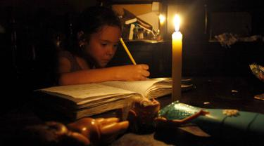 Seorang anak belajar dengan menggunakan lilin akibat pemadaman listrik di San Cristobal, Venezuela, Senin (25/4). Venezuela menerapkan pemadaman listrik selama empat jam sehari untuk menghadapi krisis energi yang memburuk. (REUTERS/Carlos Eduardo Ramirez)