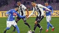 Striker Juventus, Cristiano Ronaldo, berusaha melewati pemain Napoli pada laga Serie A di Stadion San Paolo, Minggu (3/3). Juventus menang 2-1 atas Napoli. (AP/Ciro Fusco)