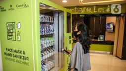 Pengunjung melihat vending machine penjual masker di mal Central Park, Jakarta, Kamis (11/6/2020). Selain menerapkan protokol kesehatan ketat, pusat perbelanjaan juga menyediakan fasilitas pendukung 'physical distancing' sebagai persiapan operasional di era normal baru. (Liputan6.com/Faizal Fanani)