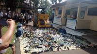 Nampak alat berat tengah memusnahkan ribuan botol miras hasil razia polres Garut (Liputan6.com/Jayadi Supriadin)