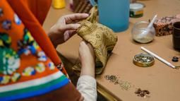 Pekerja menjahit baju untuk wayang kayu khas Sunda atau wayang golek di galeri kerajinan tangan Cupumanik di Bandung, 17 Februari 2020. Galeri kerajinan tangan Cupumanik memproduksi berbagai wayang golek untuk dijual sebagai cendera mata bagi wisatawan lokal maupun asing. (Xinhua/Septianjar)