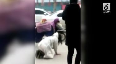 Seorang wanita merangkak pada sebuah jalanan ramai di China. Padahal sang pacar ada di sebelahnya sambil berjalan santai.