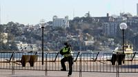 Seorang pejabat keamanan berdiri di depan Harbour Bridge, Sydney, Australia, Selasa (13/7/2021). Lima juta penduduk Sydney akan berada dalam lockdown COVID-19 untuk dua minggu lagi. (Brendon THORNE/AFP)