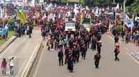 Massa buruh berjalan memasuki ruas Jalan Medan Merdeka Barat saat perayaan hari Buruh Internasional di Kawasan Patung Patung Arjuna Wiwaha, Jakarta, Senin (5/1). Ribuan massa buruh ikut dalam perayaan MayDay 2017. (Liputan6.com/Helmi Fithriansyah)