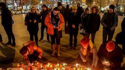 Sejumlah orang menyalakan lilin di depan foto jurnalis investigasi Slovakia Jan Kuciak di Wenceslas Square di Praha (26/2). Mereka berkumpul sambil menyalakan lilin untuk memberi penghormatan kepada Jan Kuciak. (AFP Photo/Michal Cizek)