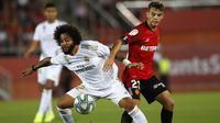 Bek Real Madrid, Marcelo, berebut bola dengan bek Real Mallorca, Jose Raillo, pada laga La Liga Spanyol di Stadion Iberostar, Mallorca, Sabtu (19/10). Mallorca menang 1-0 atas Madrid. (AFP/Javier Reina)