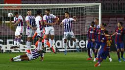 Striker Barcelona, Lionel Messi, melepaskan tendangan bebas ke gawang Real Valladolid pada laga Liga Spanyol di Stadion Camp Nou, Selasa (6/4/2021). Barcelona menang dengan skor 1-0. (AP Photo/Joan Monfort)
