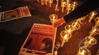 Poster terpidana mati Mary Jane diletakan di dekat lilin saat aksi gabungan komunitas buruh migran di depan Istana Merdeka, Jakarta, Minggu (26/4/2015). Aksi itu menyerukan penolakan atas hukuman mati di Indonesia. (Liputan6.com/Faial Fanani)