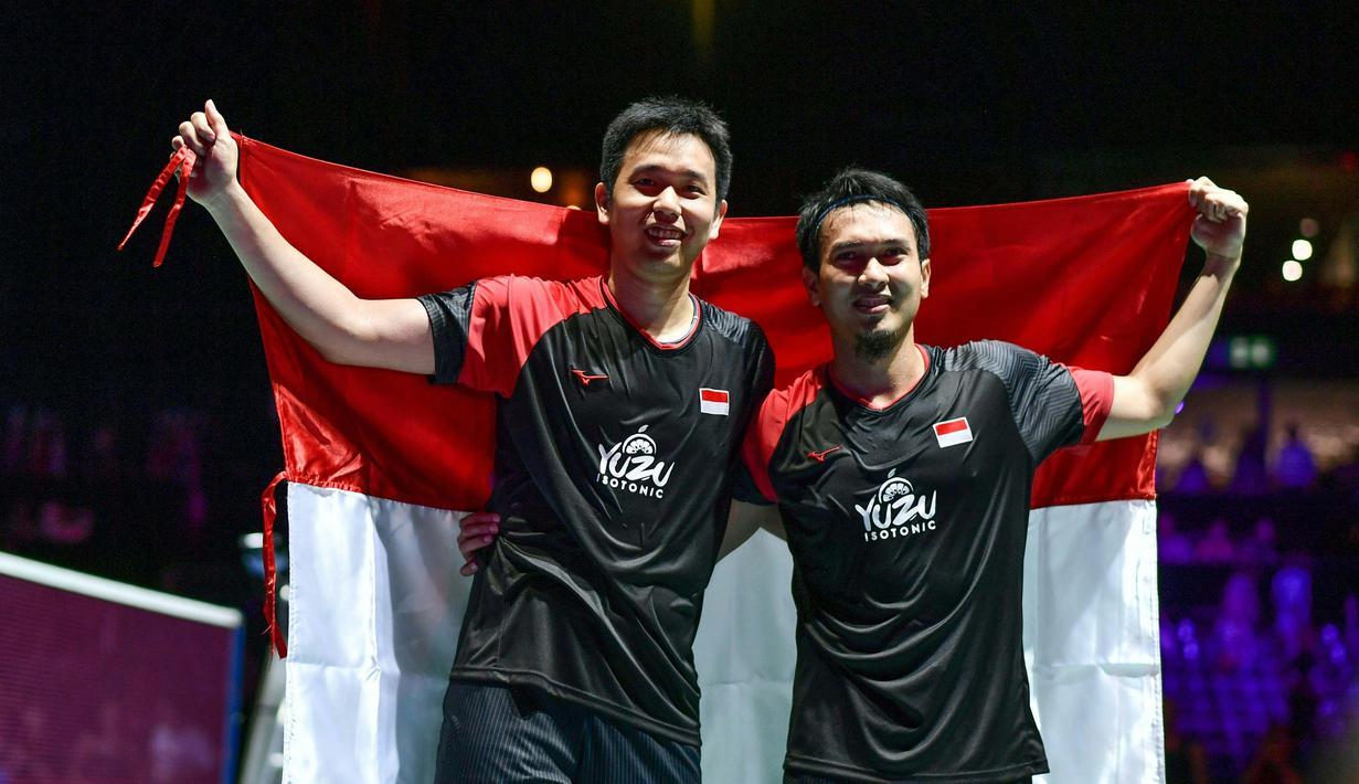 Pasangan Indonesia, Hendra Setiawan/Mohammad Ahsan melakukan selebrasi usai menjuarai Kejuaraan Dunia Bulutangkis 2019 setelah mengalahkan wakil Jepang, Takuro Hoki/Yugo Kobayashi, Minggu (25/8). Indonesia menang 25-23, 9-21, 21-15. (AFP/Fabrice Coffrini)