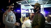 Jajaran Polresta Bandung sedang menggelar patroli dini hari dengan sasaran para pedagang warung makan dan pedagang minuman di wilayah Soreang, Kabupaten Bandung, Minggu (18/7/2021). Dalam kesempatan itu, petugas turut membagikan sembako.