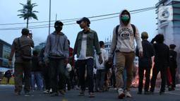 Sekelompok anak muda melintasi kawasan Gondangdia, Jakarta, Kamis (8/10/2020). Massa gabungan berunjuk rasa menentang disahkan Omnibus Law UU Cipta Kerja. (Liputan6.com/Helmi Fithriansyah)