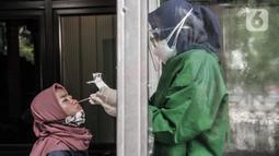 Tenaga kesehatan saat melakukan tes antigen di Terminal Kampung Rambutan, Jakarta, Minggu (3/1/2021). Pengelola Terminal Kampung Rambutan menyediakan tes antigen bagi penumpang yang baru tiba jika tidak memiliki surat kesehatan dengan harga Rp150 ribu per orang. (merdeka.com/Iqbal S. Nugroho)