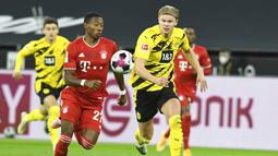 Pemain Bayern Munchen, David Alaba, berebut bola dengan striker Borussia Dortmund, Erling Haland, pada laga Bundesliga di Stadion Signal Iduna Park, Sabtu (7/11/2020). Bayern menang dengan skor 3-2. (Bernd Thissen/Pool via AP)