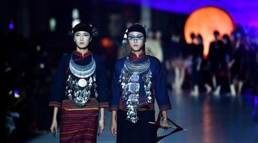 Dua model memeragakan kreasi busana yang terbuat dari brokat Li, pakaian tradisional yang dibuat oleh kelompok etnis Li, dalam sebuah peragaan busana di Haikou, Provinsi Hainan, China selatan, pada 19 November 2020. (Xinhua/Guo Cheng)