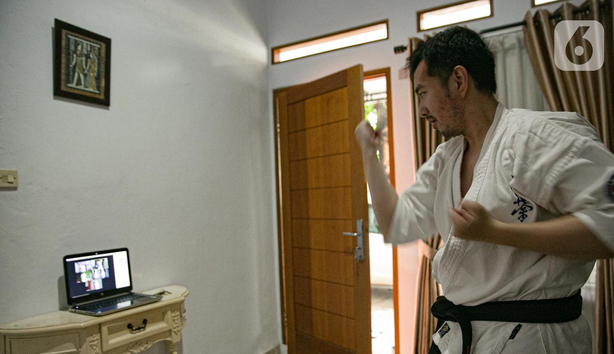 Charlie (28) instruktur karate mengajar murid secara virtual di Jakarta, Sabtu (13/2/2021). Sejak bulan Maret murid-murid berlatih di rumah secara vitual guna mencegah penyebaran virus Covid-19. (Liputan6.com/Faizal Fanani)