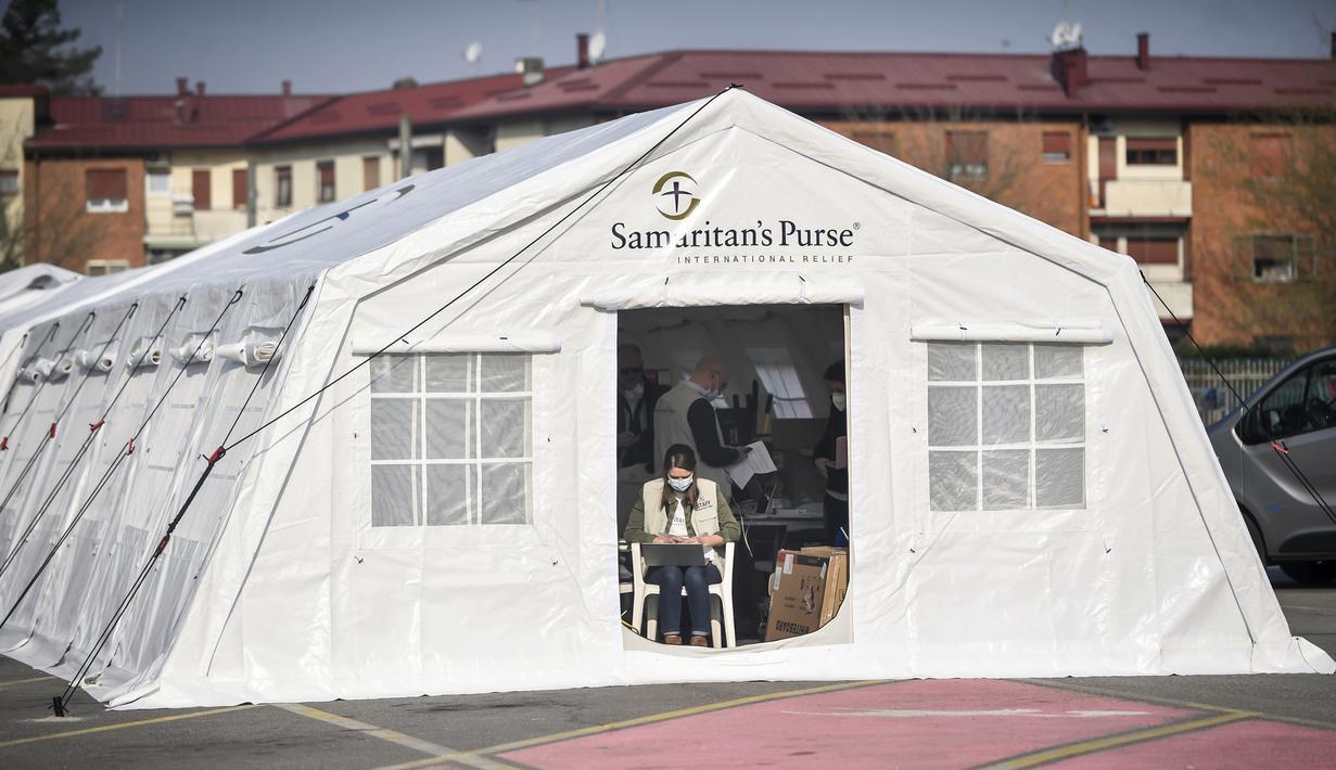 Petugas medis bekerja di rumah sakit lapangan darurat Samaritan's Purse di Cremona, Italia, Jumat (20/3/2020). Rumah sakit lapangan ini dibangun untuk merawat pasien virus corona COVID-19 yang terus melonjak. (Claudio Furlan/LaPresse via AP)