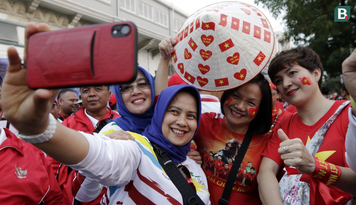 Suporter Timnas Indonesia U-22 dan Vietnam U-22 bernyanyi bersama jelang laga final SEA Games 2019 di Stadion Rizal Memorial, Manila, Selasa (10/12). Meski bersaing para suporter tetap akrab. (Bola.com/M Iqbal Ichsan)