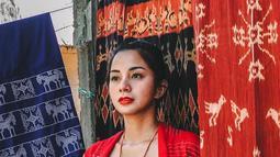 Pesonanya semakin terpancar kala memakai kebaya ombak laut semanggi merah. Berfoto dengan latar belakang kain tenun ikat Sumba, ibu satu anak ini tampak awet muda di usianya ke 32 tahun. (Liputan6.com/IG/@kiranalarasati)