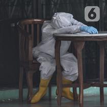 Tenaga kesehatan tidur kelelahan di sela bertugas di Graha Wisata TMII, Jakarta, Selasa (22/6/2021). Lonjakan kasus aktif Corona menyebabkan kapasitas kamar isolasi pasien OTG Covid-19 di Graha Wisata TMII telah terisi penuh usai pada hari ini tercatat kedatangan 6 pasien. (merdeka.com/Iqbal S Nugro