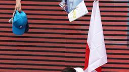 Petenis Jepang Naomi Osaka menandatangani bendera yang disodorkan penonton usai mengalahkan petenis Republik Ceko Marie Bouzkova pada Australia Terbuka di Melbourne, Australia, Senin (20/1/2020). Penonton menyodorkan topi, bendera, hingga bola untuk ditandatangani Naomi. (AP Photo/Lee Jin-man)