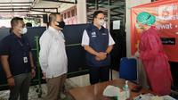 Gubernur DKI Jakarta, Anies Rasyid Baswedan (kanan), Dewan Kota Jakarta Timur Dani Taufik dan Sekretaris Perusahaan Bank DKI Herry Djufraini berbincang dengan petugas medis di vaksin keliling yang di inisiasi Pemprov DKI Jakarta, di Jakarta, Minggu (31/07/2021). (Liputan6.com/HO/Helmi)
