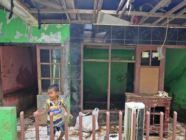 Seorang anak bermain di rumah yang rusak akibat terjangan banjir di kawasan  Balekambang, Kramatjati, Jakarta Timur, Selasa (30/4/2019). Sejumlah rumah warga di RT 005/RW 005 Balekambang rusak diterjang banjir yang terjadi pada 27 April 2019 lalu.(Www.sulawesita.com)