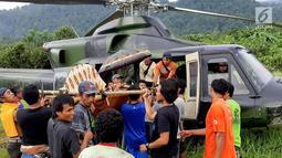 Warga mengevakuasi Heriani yang akan melahirkan saat tiba menggunakan helikopter di Dusun Air Teh, Sulawesi Tengah, Sabtu (27/7/2019). Evakuasi berawal saat Tim Penerbad menerima perintah untuk melakukan dorongan logistik bagi pasukan Satgas Tindak. (Liputan6.com/HO/Satgas TNI-Tinombala)