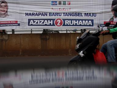 Pengedara melintas di depan alat peraga kampanye (APK) yang terpasang di kawasan Depok, dan Ciputat, Tangerang Selatan, Minggu (18/10/2020). KPU Kota Tangsel dan Depok membagikan sejumlah alat peraga kampanye kepada pasangan calon Pilkada 2020 serentak. (Liputan6.com/Johan Tallo)