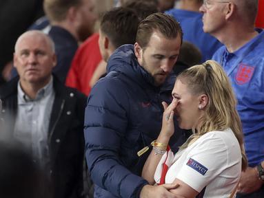 Pemain Inggris Harry Kane memeluk istrinya Katie Goodland atau Kate pada akhir pertandingan final Euro 2020 antara Inggris dan Italia di Stadion Wembley, London, Inggris, Minggu (11/7/2021). Italia mengalahkan Inggris 3-2 dalam adu penalti. (Carl Recine/Pool Photo via AP)