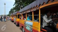 Pengelola Monas menyediakan mobil gandeng untuk berkeliling di kawasan Monas, Jakarta, Sabtu (26/12/2015). Akses yang mudah dan harga yang murah menjadi alasan warga menjadikan Monas tujuan wisata mereka. (Liputan6.com/Yoppy Renato)