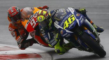 Pembalap Yamaha MotoGP Valentino Rossi (depan) saat beradu cepat dengan saingan terberatnya pembalap Honda Marc Marquez selama Grand Prix Inggris di sirkuit Silverstone (30/8/2015). Valentino Rossi finis pertama di seri ke-12 ini. (REUTERS/Darren Staples)