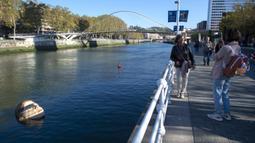 Dua wanita mengambil gambar patung Bihar karya seniman hiperrealis asal Meksiko Ruben Orozco terendam di Sungai Nervion, Kota Bilbao, Basque, Spanyol, 14 Oktober 2021. Bihar diambil dari kata dalam bahasa Basque yang artinya 'besok'. (ANDER GILLENEA/AFP)