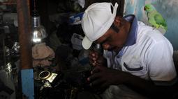Joseph Sekar saat memperbaiki kamera di Chennai, India, Jumat (17/3). Pekerjaan sehari-hari Joseph Sekar adalah menerima jasa perbaikan kamera. (AFP PHOTO / ARUN Sankar)