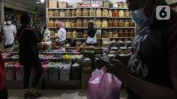 Calon pembeli memilih berbagai jenis kue kering yang dijual di Pasar Mayestik, Jakarta, Senin (3/5/2021). Omzet penjualan kue kering menjelang Lebaran tahun ini mengalami peningkatan hingga 70 persen dari tahun sebelumnya yang mengalami penurunan hingga 70 persen. (Liputan6.com/Johan Tallo)