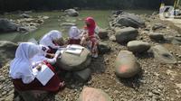 Siswa kelas 3 SDN II Roda Kota Bogor dan pendamping belajar kelompok secara daring di pinggir sungai Ciliwung, Kampung Kebon Jukut RT 01/10, Babakan Pasar, Kamis (6/8/2020). Belajar di pinggir sungai Ciliwung itu guna mendapatkan jaringan internet yang baik di masa pandemi. (merdeka.com/Arie Basuki)