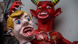 Patung setan yang memegang kepala Presiden AS Donald Trump disiapkan warga sebelum perayaan pembakaran Yudas di Mexico City, Meksiko (15/4). Warga setempat membuat patung Trump dari kertas dan membakarnya saat perayaan Paskah. (AP Photo/Rebecca Blackwell)