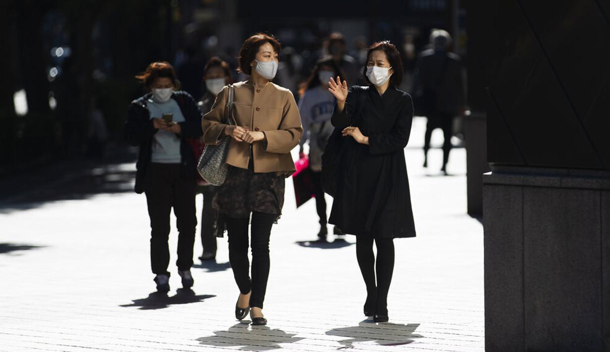 Wanita dengan masker wajah berjalan di Tokyo, Jepang, Jumat (16/10/2020). Ibu Kota Jepang itu mengonfirmasi lebih dari 180 kasus virus corona COVID-19 baru pada hari Jumat. (AP Photo/Hiro Komae)